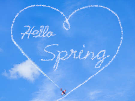 Sign of spring. Hello springtime, word written by a acrobatic plane. Montage