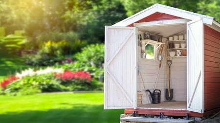 Opslagschuur gevuld met tuingereedschap. Prachtige groene botanische tuin op de achtergrond. Kopieer ruimte voor tekst- en productweergave. Stockfoto