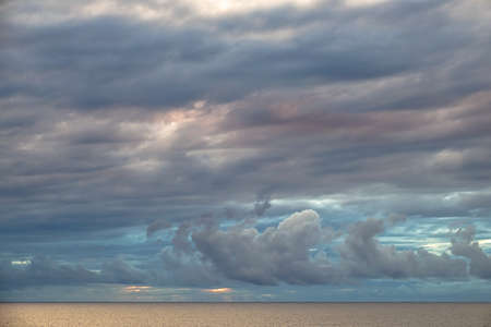 Colorful clouds over calm ocean at sunset.