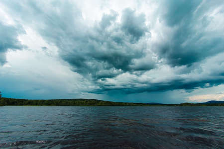 Dramatic sky over a lake close to Soderhamn and Hudiksvall in Sweden. Dark blue stormy clouds reflected in the dark water. Zdjęcie Seryjne