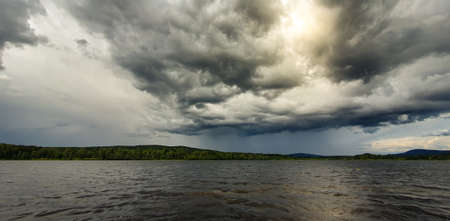 Dramatic rainy sky over a lake close to Soderhamn and Hudiksvall in Sweden. Dark blue stormy clouds and the sun shining through.