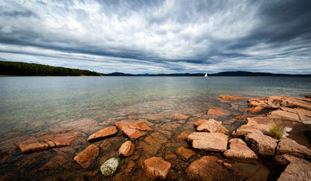 Lonely sail boat in archipelago. Dramatic sky over stony beach coast and shallow water. Storsand, High Coast in northern Sweden.