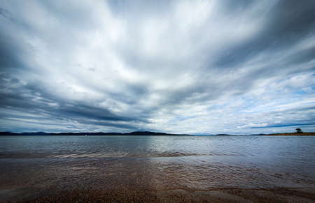 Dramatic sky over beautiful calm water in Gulf of Bothnia. Storsand, High Coast in northern Sweden. Zdjęcie Seryjne