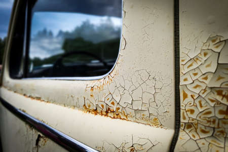 Old rusty wrecked car. Close up of cracked and peeling paint.