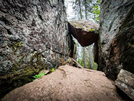 Natural rock formation, big stone stuck between two rocks in the Skule forest, High Coast in northern Sweden. Zdjęcie Seryjne
