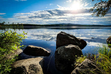 Beautiful sunset in forest mountain landscape. Lake and rocks in foreground. Angersjon between Hudiksvall and Soderhamn in Sweden.