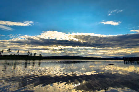 Beautiful sunset reflected in the calm water. Lake Angersjon between Hudiksvall and Soderhamn in Sweden. Zdjęcie Seryjne