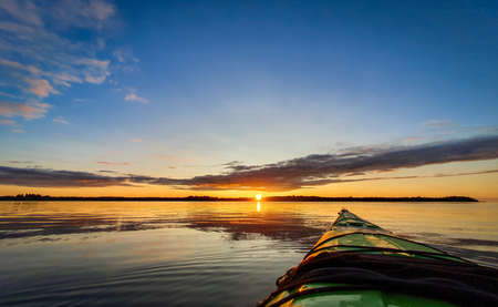Paddling a sea kayak at sunset, calm water. Zdjęcie Seryjne