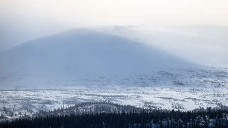 Winter landscape with foggy snowy mountains.