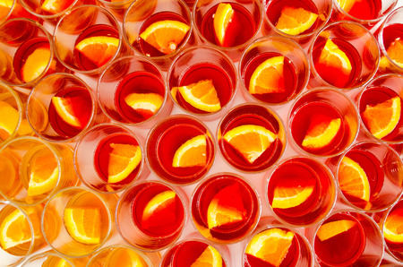 Many glasses of fresh alcoholic welcome drinks with pieces of oranges
