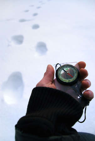 Hand with a compass against traces on snow