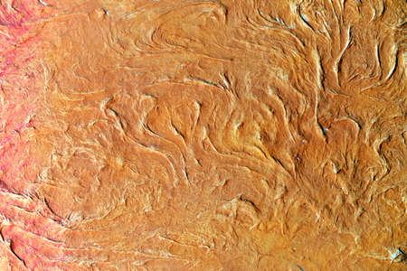 Embossed surface with curls of orange color