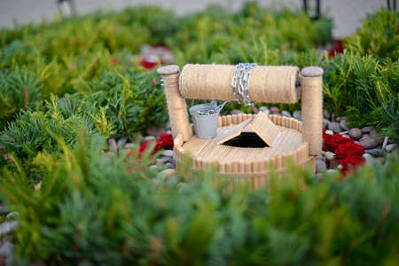 Decorative well in flower arrangement with coniferous branches Stock Photo