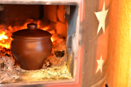 Cooking in a wood stove on fire Stock Photo