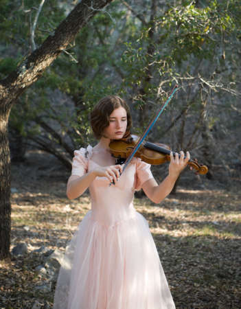 violins: A pretty young womanteenager in a vintage dress holding a violin and bow in a woodland setting. Subject is backlit, and photo has a nostalgic feel. Plenty of background at top of picture for type, etc.