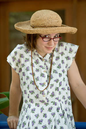Pretty young girl wearing a straw hat and tortoise shell frame glasses in a flower-print vintage dress. Sunny, outdoor setting photo