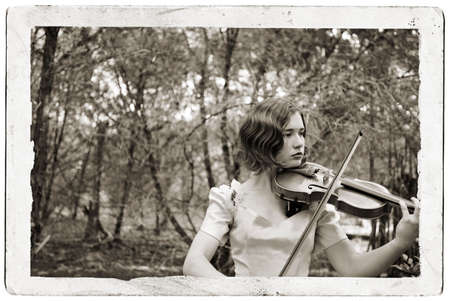 Monotone photo of pretty girl in an antique party dress playing the violin in the woods composited with scan of an old postcard photo