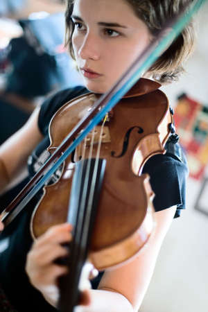 violins: Pretty teenage girlyoung woman playing the violin; closeup shot, soft focus, short depth of field Stock Photo