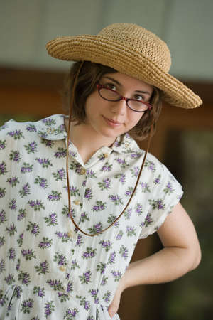 straightforward: Portrait of a pretty young woman or teenager in a straw hat looking over the top of her glasses, in a flowered vintage dress Stock Photo