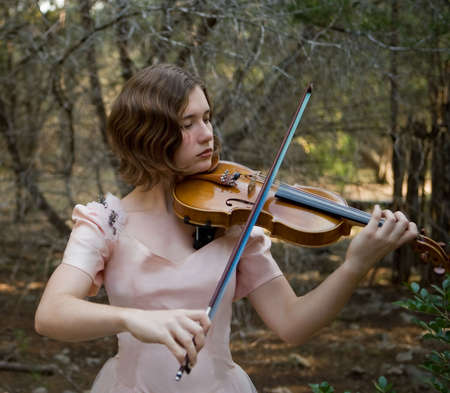 Pretty young woman playing the violin in a forest wearing a pink vintage evening gown. Short depth of field. photo
