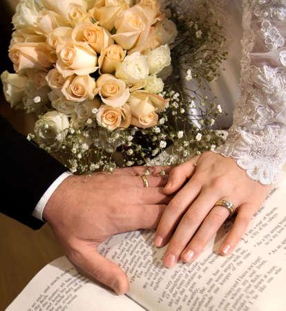 신부와 신랑의 손에 백그라운드에서 샴페인 장미와 성경을 만지고