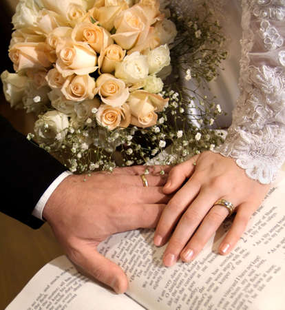 Bride and Grooms hands touching on the Bible, with champagne roses in the background Stock Photo