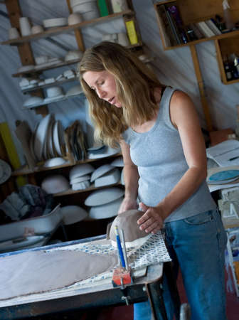 ceramicist: Woman working in her pottery studio, pottery on shelves in background