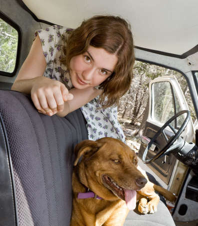 A young woman in an old pickup truck with her beloved dog photo