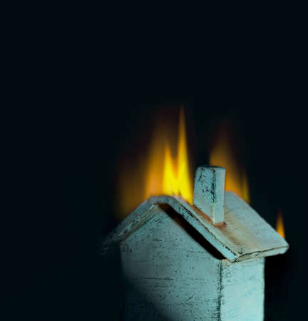 Burning toy house; metaphor for loss, crisis, insurance, real estate, danger
