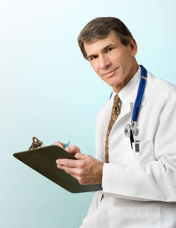 Friendly handsome doctor writing out prescription, stethoscope around neck. Soft color plain background