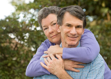 Healthy retired couple hugging outdoors, closeup, looking at camera Stock Photo