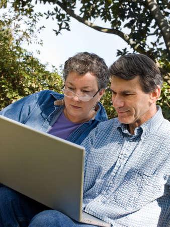 Happy mature couple using the laptop, outdoors, closeup photo