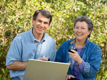 Happy mature couple enjoying wine and planning their retirement options.