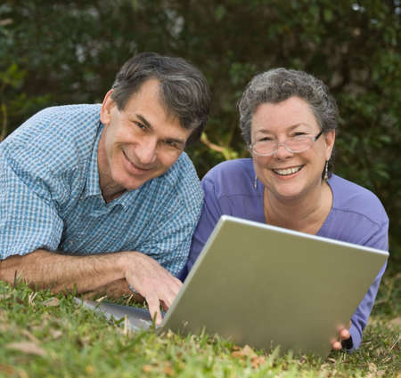 Happy, cute retired couple lying in the grass working on their laptop in an outdoor setting photo