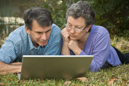 Attractive senior couple working together on the computer in an outdoor setting. Stock Photo - 2550985