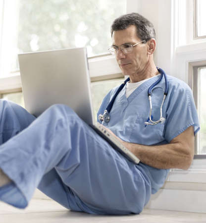 Doctor or surgeon in blue scrubs, sitting on floor on break, catching up on his laptop. photo