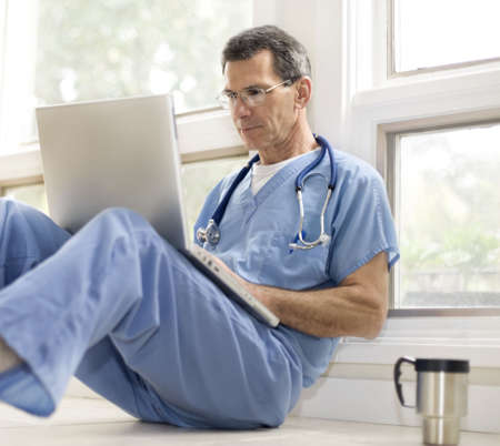 Doctor or medical worker taking a coffee break, sitting on floor with laptop photo