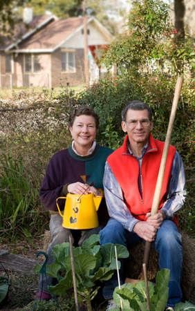 Mature couple sitting on bale of hay in their city garden with collard plants in the foreground.