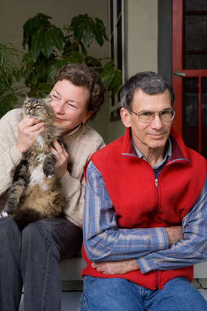 Mature woman lavishes affection on her cat, ignoring impatient husband. photo