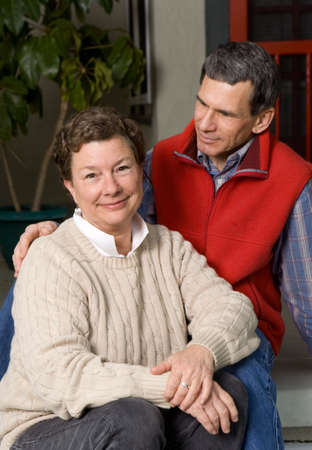 Late middle age, mature, senior couple portrait on front porch. Man gazing lovingly at woman photo