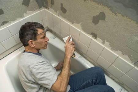 handtools: Man working in a tight space while applying ceramic tile to a bathtub enclosure wall. Viewed looking down.