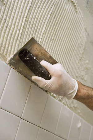 Closeup of mans hand holding a trowel, applying mortar for tiling a wall. Selective focus.