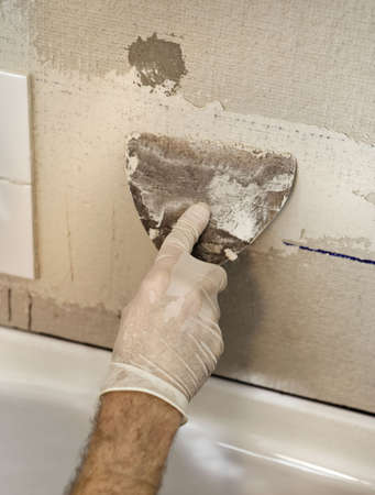 Closeup of a man's hand applying mortar to a bathtub enclosure wall that he is tiling.