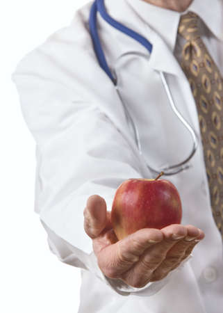 Doctor holding an apple. Closeup and sharp focus on hand and apple. Stock Photo