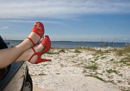 sea sexy: Womans legs with red patent leather spike heels dangling out the car window parked at the beach Stock Photo