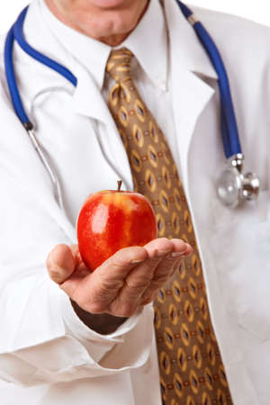 Doctor in white lab coat offering a bright red apple as a symbol of good nutrition photo