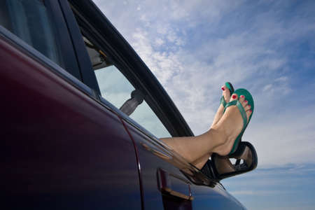 flops: Womans legs with bright green flip-flops (sandals) dangling out a car window parked at the beach