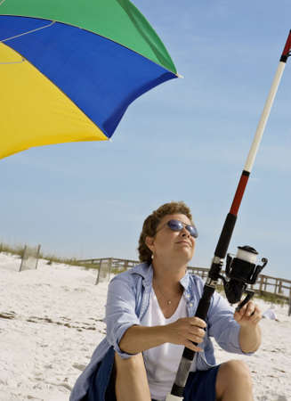 Mature woman checking her line while fishing, seated on a sandy beach Stock Photo - 3030172