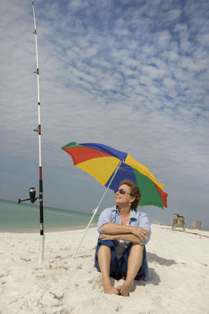 Mature woman relaxing on a white sandy beach waiting for the fish to bite. Stock Photo - 3030175