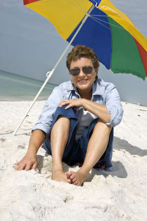 Mature woman seated on a white sandy beach enjoying the whole experience. Stock Photo - 3030178